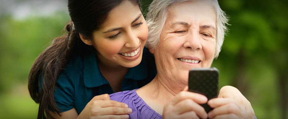 Young lady showing an older lady how to use a smart phone